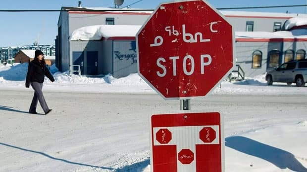 A stop sign in Iqaluit shows both English and Inuktitut. A group of Inuit women are trying to develop Inuktitut words for sexual health issues.