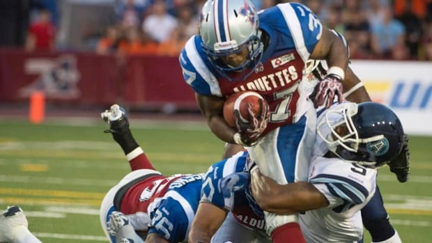 Montreal Alouettes' Tyrell Sutton is taken down by Toronto Argonauts' Jermaine Gabriel during the first half Thursday.