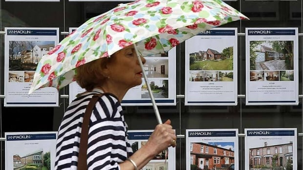 A woman walks past signs for homes for sale at a real estate agency. The industry is urging caution as Canada's banking regulator is reportedly considering tinkering with mortgage rules again.