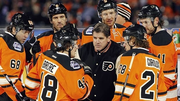 Philadelphia Flyers coach Peter Laviolette huddles with his team late in the third period of the NHL Winter Classic hockey game against the New York Rangers in Philadelphia.