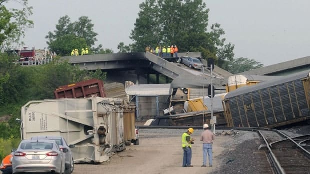 Officials survey the scene just east of the Route M overpass where several train cars derailed on the Burlington Northern Santa Fe train near Rockview, Mo. on Saturday.