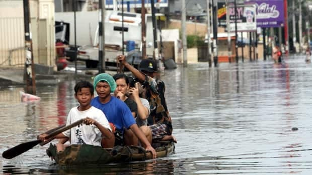 Local residents ride on a bamboo raft in a flooded street in northern Jakarta, Indonesia, Friday.