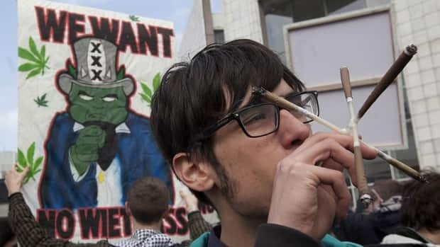 A man smokes five marijuana joints at once during a protest in Amsterdam Friday against a government plan to stop foreigners from buying marijuana in the Netherlands.