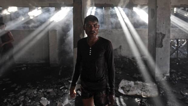 A Bangladeshi worker walks inside a two-storied garment factory that caught fire in Dhaka, Bangladesh, Saturday, Jan.26, 2013.