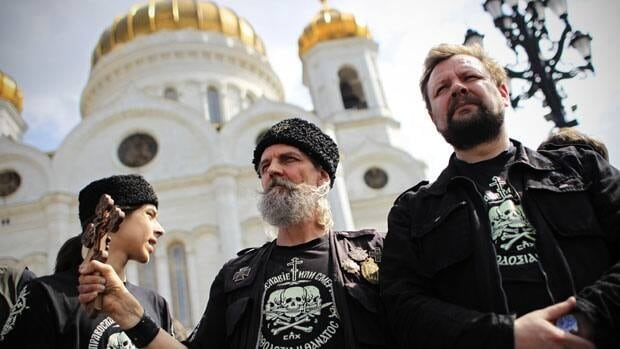 Members of an Orthodox militant group stand guard in front of the Moscow's Christ the Savior Cathedral to prevent activists from entering the cathedral to stage a protest prayer on Sunday.