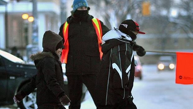 A crossing guard guides children in Winnipeg in 2009.  While 58 per cent of parents walked to school when they were children, only 28 per cent of their own kids were doing the same today, a new survey suggests.
