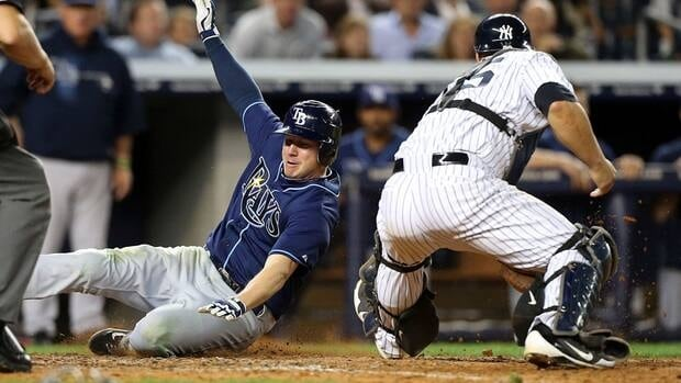 Elliot Johnson of the Tampa Bay Rays, left, slides at home to score a run against the New York Yankees at Yankee Stadium on September 14, 2012.