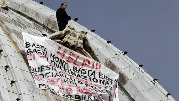 "Italian businessman Marcello di Finizio stands above his banner which reads in Italian ""Help!! Enough Monti (Italian Premier Mario Monti), enough Europe, enough multinationals, you are killing all of us. Development?? This is a social butchery!!,"" as he protests on the dome of St. Peter's Basilica at the Vatican, ."