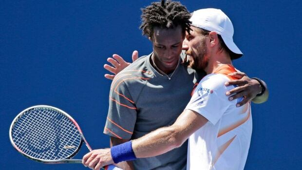 Gael Monfils, left, is embraced by Jurgen Melzer after the former retired because of injury in the Winston-Salem Open final in Winston-Salem, N.C., on Saturday.
