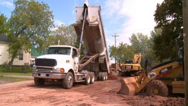 Construction crews tear up the road to install new pipes.