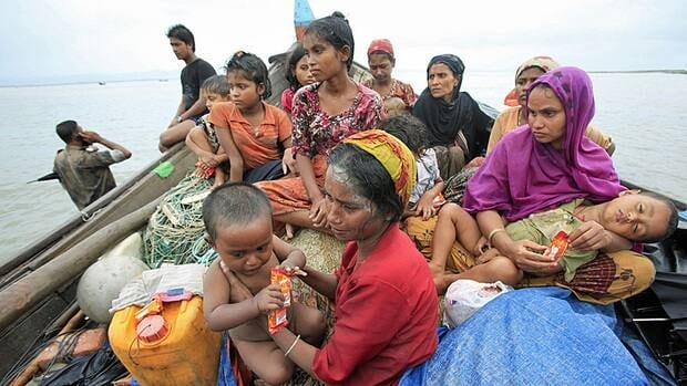 Fleeing a rise in violence in Burma's Rakhine State, Rohingya refugees sit on a boat as they try to get into Bangladesh in Teknaf on June 13. Last year, the number of refugees who fled their countries hit an 11-year high of 800,000, a UN agency says.