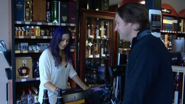 A customer makes a purchase at the Keg 'n' Cork liquor store in south Edmonton.