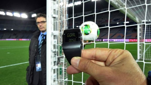 A FIFA official displays new goal-line technology developed by GoalRef for the media in Yokohama last December, which lost out to GoalControl to be used at the 2014 World Cup.
