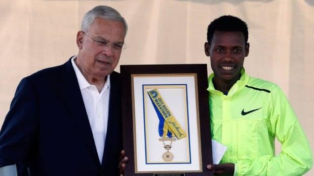 Boston Marathon 2013 men's winner Lelisa Desisa, right, of Ethiopia, holds his medal with Boston Mayor Thomas Menino after presenting it to the city as a tribute to the victims of the Boston Marathon bombings.