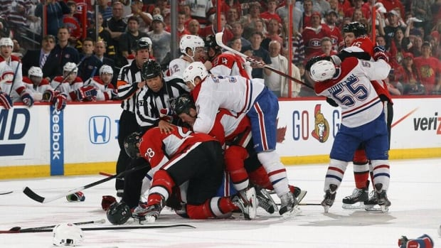 Linesman Jay Sharrers (57) and referee Paul Devorski (10) try to separate a fight between numerous Ottawa Senators and Montreal Canadiens players in Game 3 at Scotiabank Place Sunday night in Ottawa.