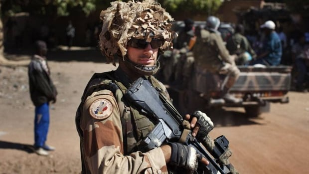 A French soldier stands guard in Diabaly, Mali on Monday. French and Malian soldiers rolled into the central towns of Diabaly and Douentza on Monday, as the U.S. started transporting French troops and equipment to Mali.
