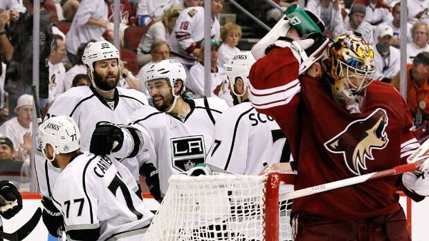 As Phoenix Coyotes goalie Mike Smith, far right, sprays water on his neck, Los Angeles Kings' Drew Doughty (8) celebrates with Rob Scuderi (7), Dustin Penner (25) and Jeff Carter (77) after a goal by Carter in the second period during Game 2 on Tuesday in Glendale, Ariz.