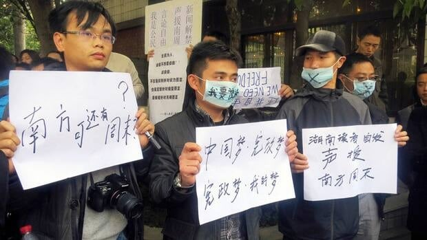 Demonstrators hold banners outside the Southern Weekly in Guangzhou on Tuesday, protesting the Communist Party's censorship of a political editorial.