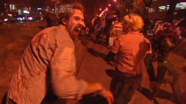 Zombies creep along the sidewalk in Winnipeg during the 2012 zombie walk.