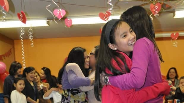 Two girls hug at one of the common celebrations within the Philipino community in Iqaluit.