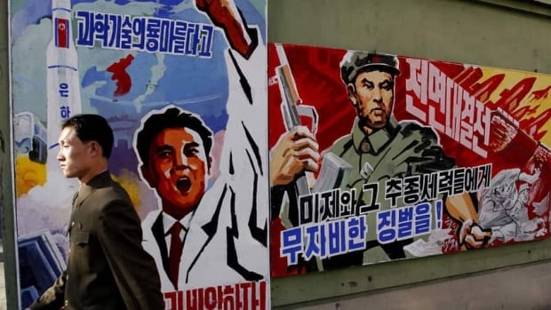 A man walks past propaganda posters in Pyongyang, North Korea. Tensions continue to mount between the two Koreas while the South and the U.S. conduct military drills.