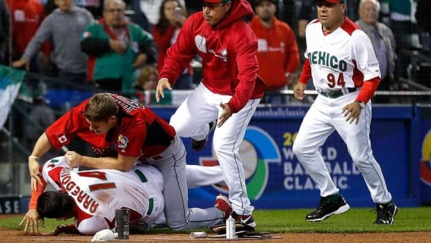 Canada's Jay Johnson, top left, and Mexico's Eduardo Arredondo fight during the ninth inning of a World Baseball Classic game, Saturday Phoenix, Ariz. (AP Photo/Matt York)
