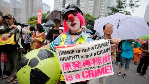A woman dressed as a clown takes part in an anti-nuclear demonstration to demand a stop to the resumption of nuclear power operations in Tokyo.