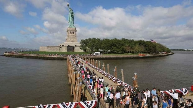Visitors to the Statue of Liberty disembark onto Liberty Island from the first ferry to leave Manhattan on Thursday. The Statue of Liberty finally reopened on the Fourth of July months after Superstorm Sandy swamped its little island in the harbour of New York City.