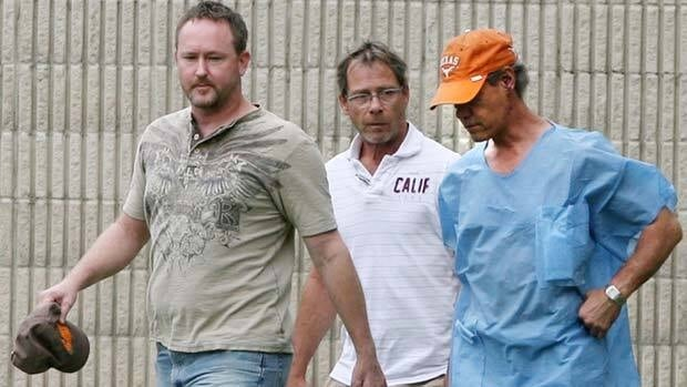 Randy Travis, far right, exits the Grayson County jail with two unknown persons Wednesday wearing scrubs and no shoes.