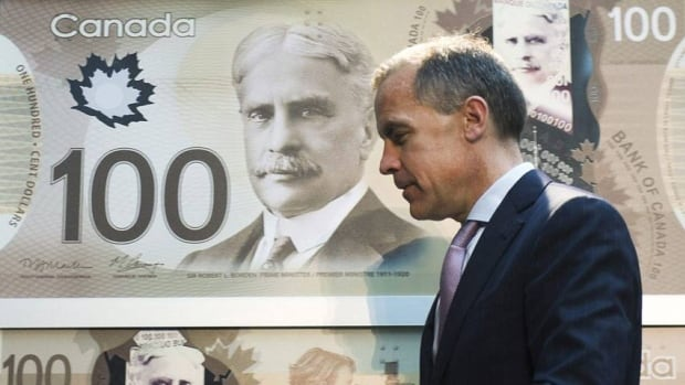 Bank of Canada governor Mark Carney presents the $100 bill, Canada's first polymer bank note, in November 2011. The new $5 and $10 notes will be unveiled Tuesday.