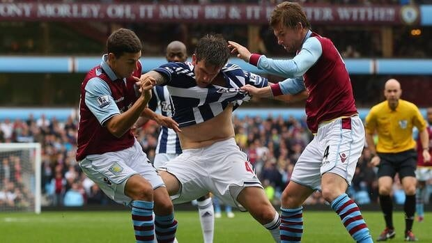 Goran Popov of West Bromwich Albion holds off Matthew Lowton and Brett Holman during their match on Sunday.
