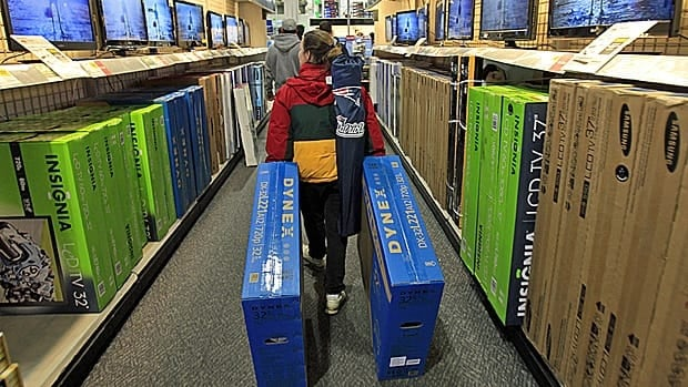 A shopper drags boxes of televisions through the aisles at Best Buy Black Friday last year. Canadians going to the U.S. to find retail bargains costs the Canadian economy at least $20 billion a year, BMO estimates.