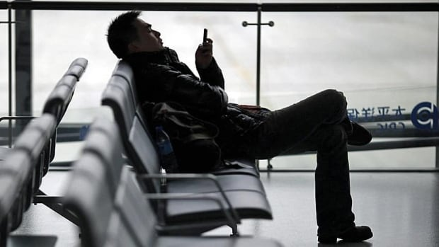 A man watches a movie on his smartphone as he waits for flight in Shanghai's airport. More and more people are watching television through non-traditional means.