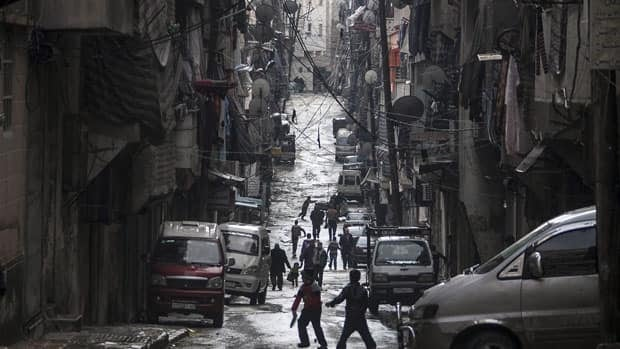 Syrians walk past damaged homes during heavy fighting between Free Syrian Army fighters and government forces in Aleppo, Syria, on Tuesday.