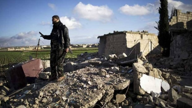 A Free Syrian Army fighter walks over the ruins of a building bombed by a Syrian Army jet in Fafeen village, north of Aleppo province, Syria, Tuesday. Rebels including Islamic extremists took full control of a sprawling military base after a bloody two-day battle.
