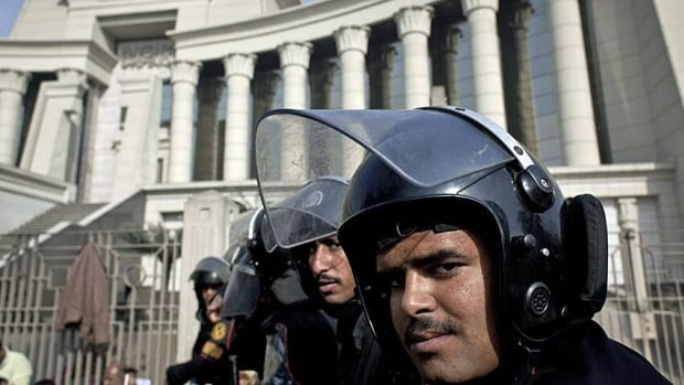 Riot policemen stand guard in front of Egypt's top court during a protest for supporters of Egyptian President Mohammed Morsi in Cairo on Monday.