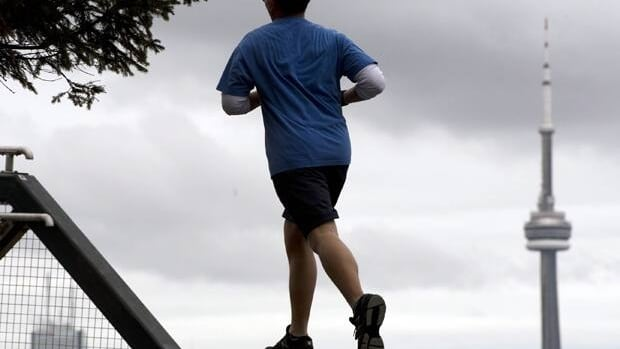 A runner in shorts rounds a bend as record-breaking temperatures hit in Toronto on Wednesday.
