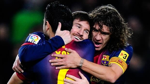 Lionel Messi receives congratulations from teammates Xavi Hernandez, left, and Carles Puyol after scoring the opening goal against Osasuna on Sunday.