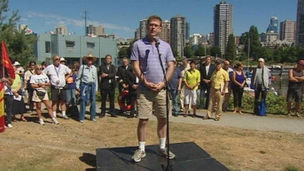 B.C. NDP Leader Adrian Dix is seen flanked by protesters on Saturday.