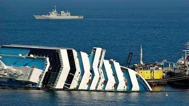 A file photo shows the half-sunken hulk of the Costa Concordia after it ran aground in Italy. Search crews have found five more bodies, raising the official death toll from the wreck to 30.
