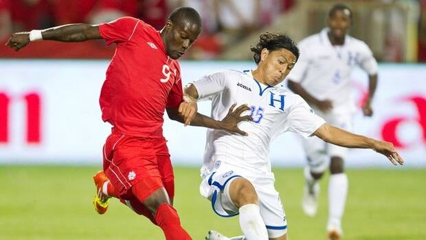 Tosaint Ricketts of Canada fights for possession with Roger Espinoza of Honduras during the FIFA 2014 World Cup Qualifier at BMO field in Toronto on June 12, 2012.