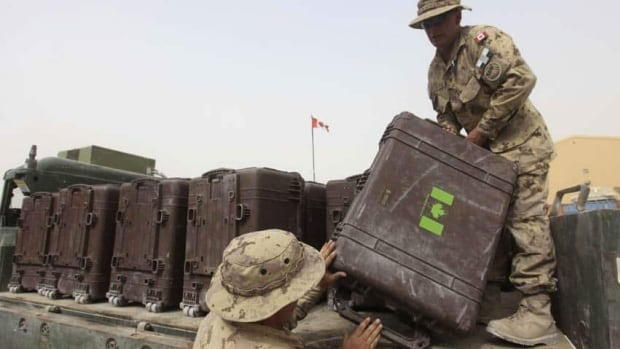 Canadians soldiers load baggage at Kandahar airbase in 2011. Hundreds of shipping containers filled with military supplies remain stranded in Afghanistan.