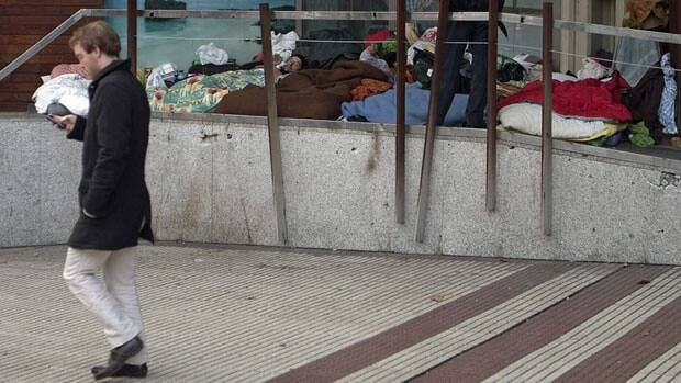 Homeless people sleep in a doorway in Madrid on Thursday.