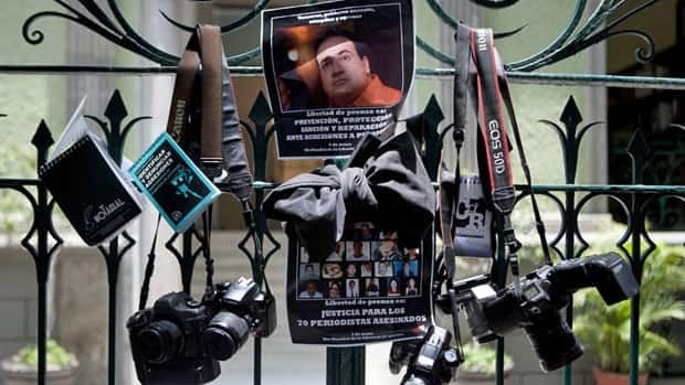 """The 23 people killed in Mexican border town Nuevo Laredo were found just one day after the mutilated bodies of three photojournalists were discovered in Veracruz. Here journalists protesting the deaths on Friday hold signs that read """"One does not kill the truth by killing the journalist."""""""