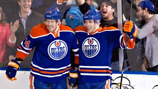 Edmonton Oilers defenceman Corey Potter, left, and Taylor Hall celebrate Hall's goal against the Vancouver Canucks in Edmonton on Saturday.