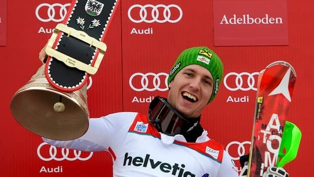 Austria's gold medalist Marcel Hirscher celebrates with a cow bell on the podium of the men's giant slalom race at the FIS Alpine Skiing World Cup on Sunday in Adelboden.