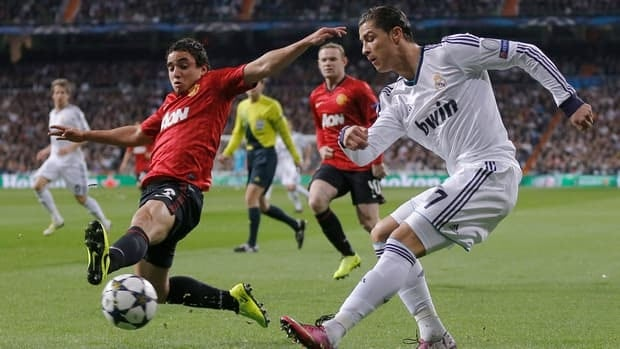 Manchester United's Rafael, left, tackles Real Madrid's Cristiano Ronaldo, right, during their match at the Santiago Bernabeu stadium in Madrid on Wednesday.