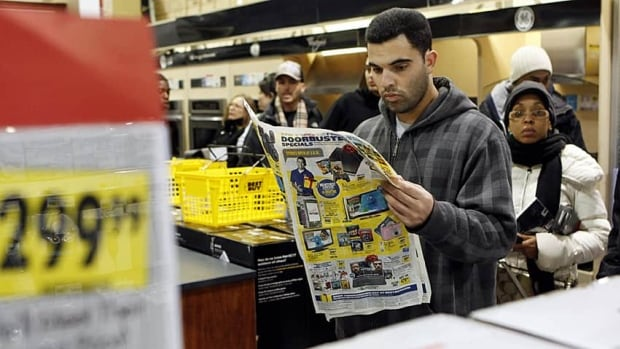 A man looks at an advertisement for Black Friday sales while waiting in line at a Best Buy electronics store in Westbury, N.Y.