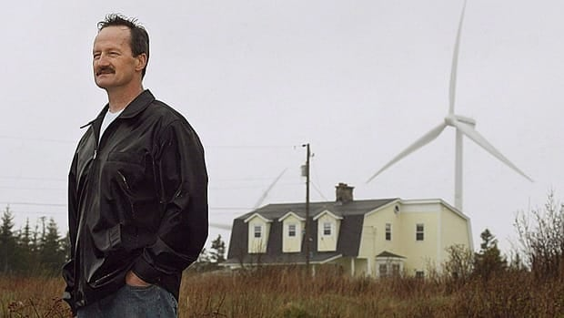 Daniel d'Entremont stands outside his house next to a 17-turbine wind farm in Lower West Pubnico, N.S., in this 2006 file photo, after his family had to move out because of noise. Health Canada is planning a study to examine the possible links between wind-turbine noise and health effects reported by people living near the structures.