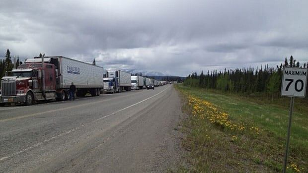 Trucks along the highway near Teslin, Yukon. They haven't been able to get through on roads because of flooding and mudslides.